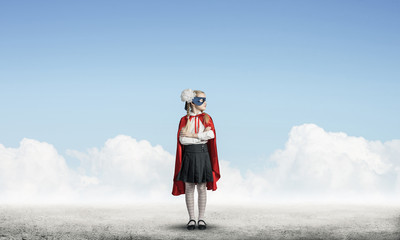 Girl power concept with cute kid guardian against cloudscape bac