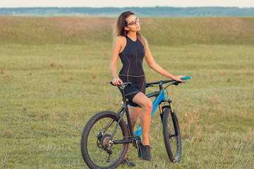 A girl riding a mountain bike on an asphalt road, beautiful portrait of a cyclist at sunset
