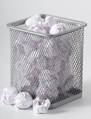 A trashcan full of crumpled paper on white background close up