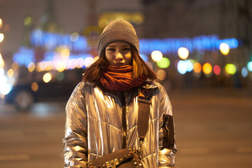 girl in a winter brilliant jacket a red scarf and hat. on the background of Christmas lights. bokeh Garlands.