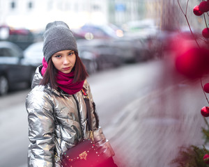 portrait of a beautiful girl on the street with new-year decorations in red colors. balls and branches, Christmas tree branches.