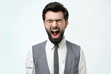 Angry spanish business man with beard screaming. Negative facial emotion.