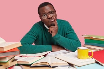 Indignant Afro American man looks in displeasure, has dark skin, wears green jumper, keeps hand near mouth, thinks about future plans, works with dictionary and textbooks, isolated on pink wall