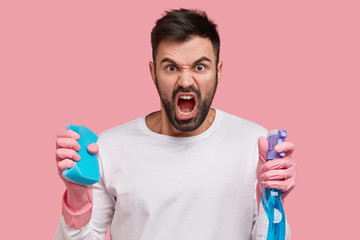 Outraged unshaven man carries blue mop and detergent, dressed in white clothes, feels angry with wife who makes him cleaning house, expresses negative emotions, models over pink studio wall.
