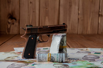 Gun and Stack of Money, drugsand lying on the hryvnia on a wooden table. Drug use, crime, addiction and substance abuse concept on wooden background