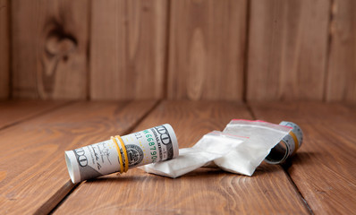 Stack of Money, drugsand on a wooden table. Drug use, crime, addiction and substance abuse concept on wooden background
