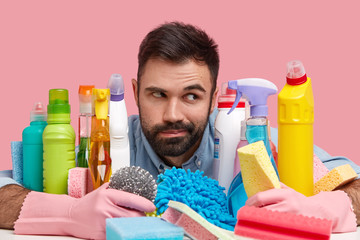 Contemplative man with dark stubble, wears rubber gloves, poses near many detergents, holds sponge, going to wash dish, scrubs bathtub, looks pensively aside, isolated over pink studio background