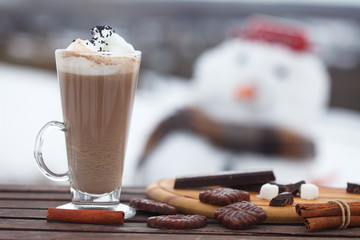 Glass of hot chocolate or cappuccino with cream and chunks of dark chocolate on  wooden table. Snow white in blurred background.