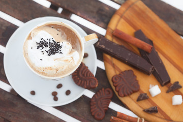 Cup of  Hot chocolate or espresso with whipped cream and cinnamon sticks, top view
