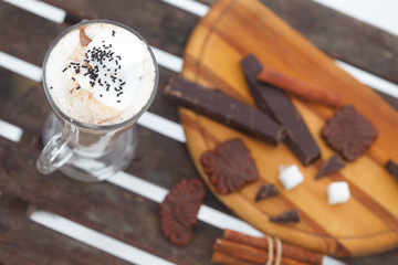 Glass of  Hot chocolate or cappuchino with whipped cream and cinnamon sticks, top view