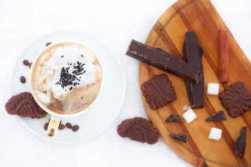Cup of esspreso or late macciato with whipped cream, cinnamon sticks, cookies and chocolate on snow. Winter refreshment.