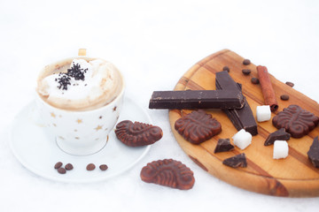 Cup of hot chocolate or coffee with whipped cream, cinnamon sticks, cookies and chocolate on snow. Winter refreshment.