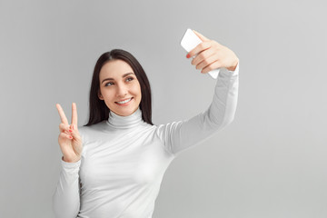 Freestyle. Woman standing isolated on gray taking selfie on smartphone showing peaace sign smiling joyful