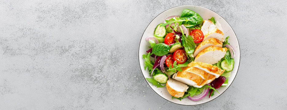 Grilled chicken breast, fillet and fresh vegetable salad of lettuce, arugula, spinach, cucumber and tomato. Healthy lunch menu. Diet food. Top view. Banner
