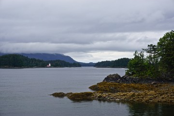 Sitka, Alaska, USA: A small lighthouse on an island in the waters off of Sitka, Alaska, under a cloudy sky.