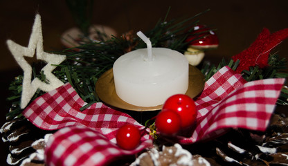 white candle and Christmas decoration over snow and wooden background, elegant shot with festive mood