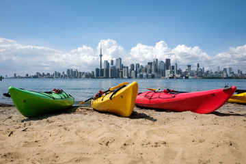 Wall Murals Toronto Colorful kayaks on a beach with Toronto skyline in background