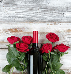 Valentines Day celebration with red wine and roses on bottom of white rustic wooden background