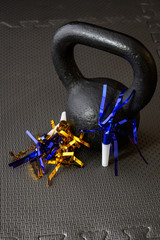 Black kettlebell on a black gym floor with blue and gold noisemakers to celebrate New Year's Eve fitness
