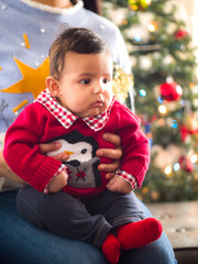 Adorable cute husky infant baby boy sits on his mother's lap as he takes holiday Christmas photos wearing a fun red collared shirt with a penguin on the front with a decorated tree in the background.