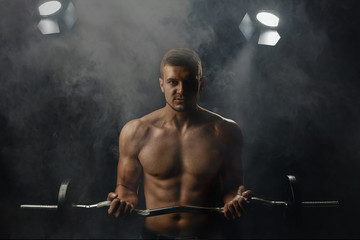 young man with a barbell posing on a dark background
