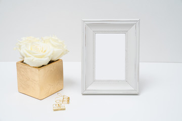 White fram and gold vase with white roses table top