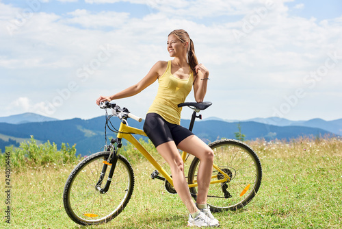 Young Happy Woman Cyclist Sitting On Yellow Mountain Bicycle