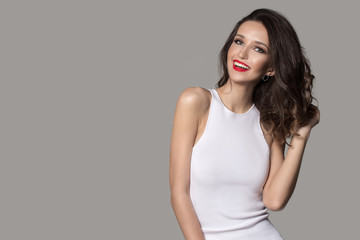 fashion woman in white dress laughs. Red lipstick and beautiful makeup. Gray background