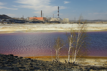 Lake with toxic waste on a background of chimneys copper smelting plant.