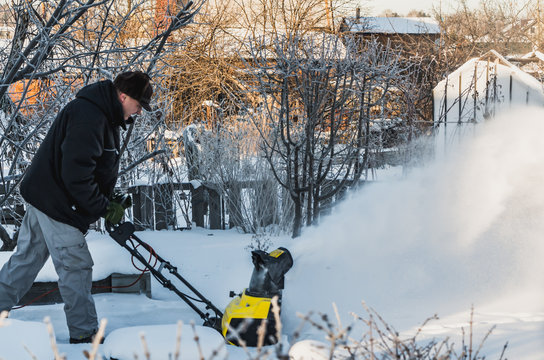 A man in a black jacket and a gray pants is brushing white snow with the yellow electric snow thrower in winter