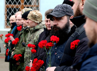 People hold red carnations during the flower lying ceremony as part of the Union of Donbass Volunteers Congress in  in Simferopol