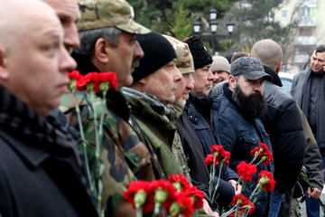 People hold red carnations during the flower lying ceremony as part of the Union of Donbass Volunteers Congress in Simferopol