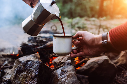 Tourists a sits near camp fire an in summer time and pours itself hot coffee during the sunset . Concept adventure active vacations outdoor. Summer camping.