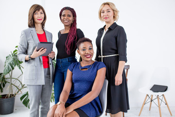 Portrait of successful multiracial women stand looking at camera, team of young employees or workers smiling posing for picture together, diverse company professionals or staff in office