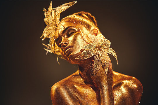 Fashion gold model woman with bright golden sparkles on skin posing, fantasy flower. Portrait of beautiful girl with glowing makeup. Glitter glowing skin, jewellery