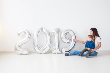 New 2019 Year is coming concept - Happy mother and son with silver colored numbers indoors.