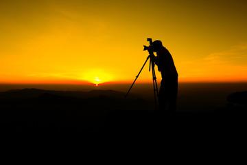 Silhouette Photographer take photo on hill Man silhouette photographer and camera shooting photo landscape sunset
