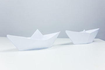 leadership concept with origami boats and swans