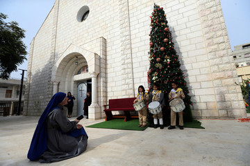 Palestinian girl scouts pose for a photo in front of a Christmas tree outside the Holy Family Church in Gaza City