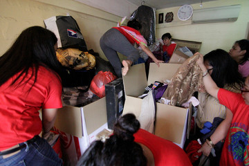 Filipina domestic workers grab free items during a giveaway of donated and dumpster dived items at the house of Singaporean freegan Colin Lau in Singapore