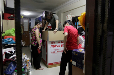 Filipina administrator Myrna Cabrera steps on items to compress them as she packs a box with donated and dumpster dived items given to her at the house of freegan Cynthia Yap in Singapore