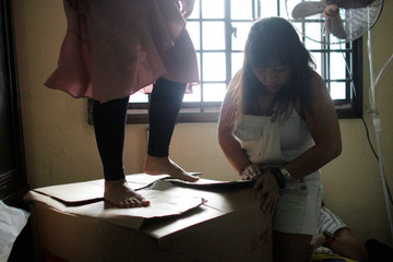 Filipina domestic workers Nanette Gumana and Hazyl Capalihan pack dumpster dived and donated items into a box that will be shipped to charities in the Philippines, at the house of Singaporean freegan Colin Lau in Singapore
