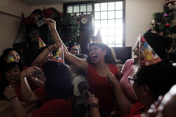 Filipina domestic worker Glendrose Gorriceta reacts after winning a free Louis Vuitton bag during a giveaway of donated and dumpster dived items at the house of Singaporean freegan Colin Lau in Singapore