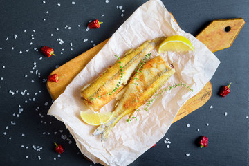 Top view of fried smelts on bake paper with lemon