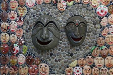 Lustige Masken aus Stein gefertigt und fröhlich bemalt