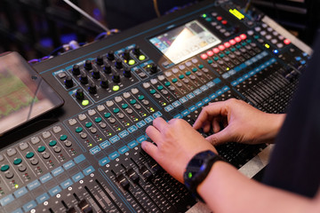 Dj controles sound controller and plays mixed edm music in the concert nightclub at a party.