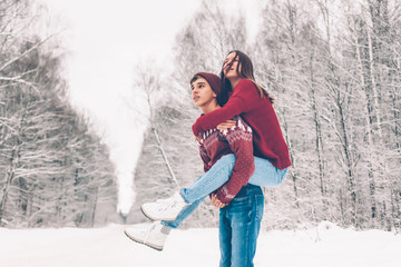 Teenagers in Christmas sweaters playing in snow in winter
