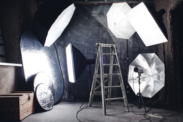 Photo hobby. Home made studio in a loft style with professional lighting, black background and ladder.