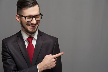 Positive businessman in glasses and formal suit smiles and points to gray background showing something useful. Place for advertising or text