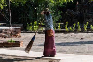 Señora limpiando con una escoba un piso en exterior de un templo en Bagan. Myanmar
